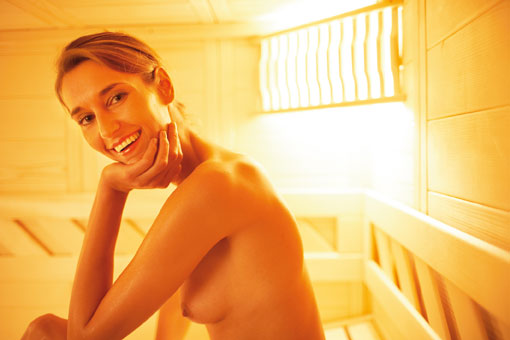 Femme nue dans une cabine de sauna